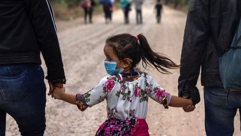 Niña de la mano de dos adultos en una marcha hacia la frontera estadounidense