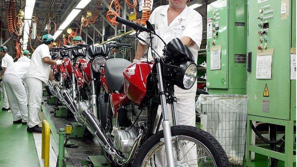 Operários e motocicletas em linha de produção da Honda
