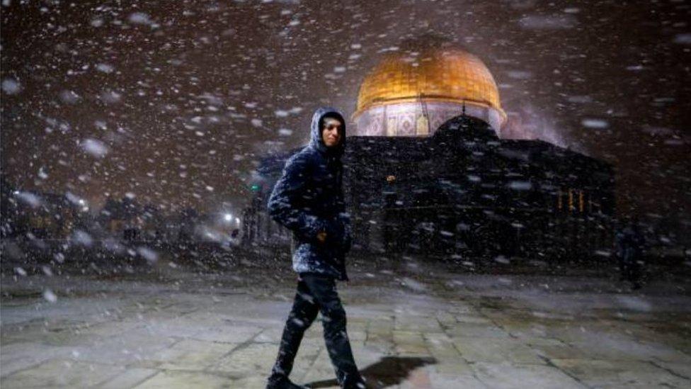 عابر أمام قبة الصخرة في المسجد الأقصى بالقدس بينما الصقيع ينهمر