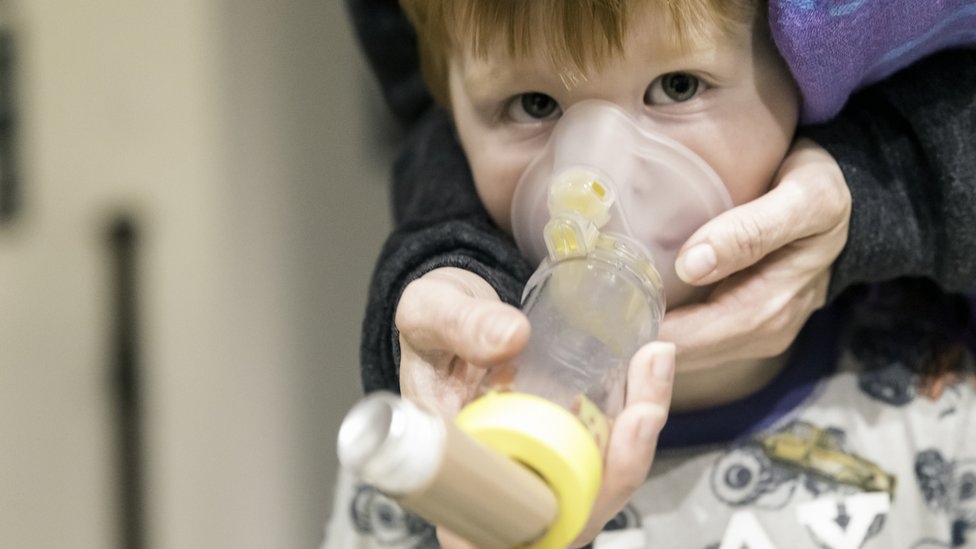 boy with asthma using a spacer device