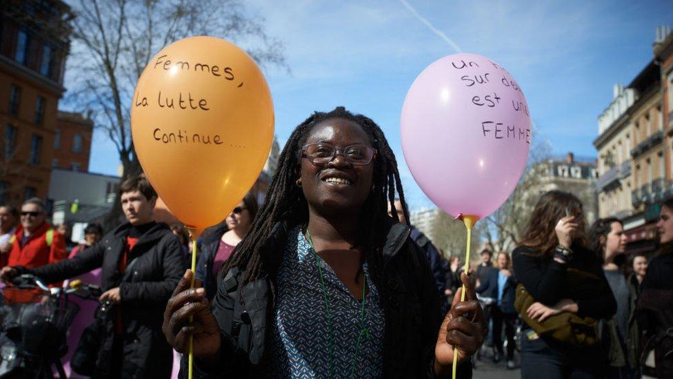 """Una mujer con un globo en el que dice """"Mujeres, la lucha continúa""""."""