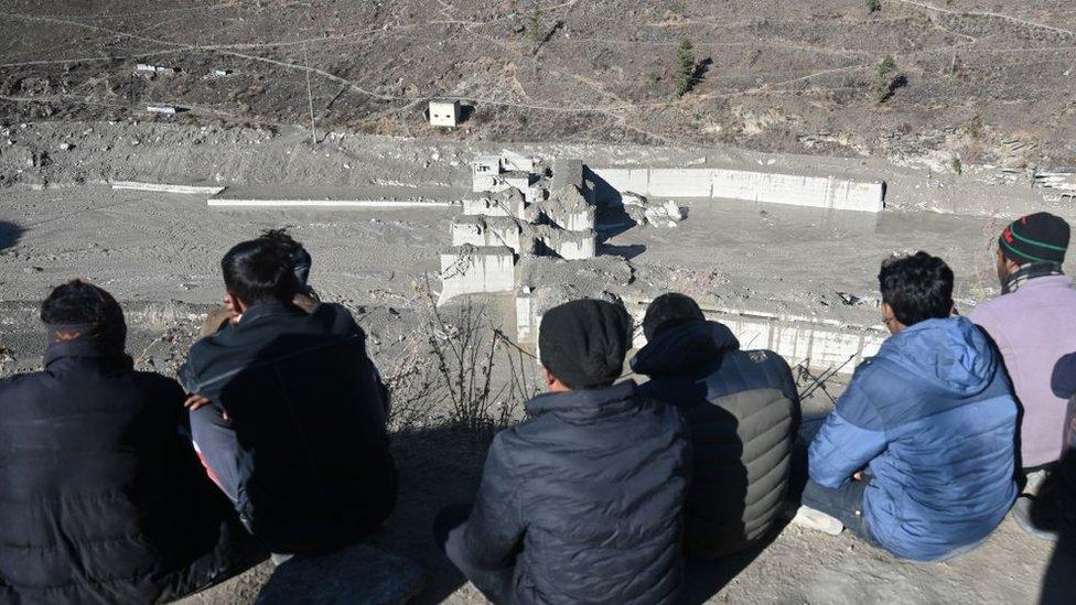Sobrevivientes del desastre de Chamoli observando los restos de una represa