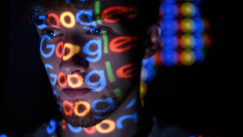 Varios logos de Google reflejados sobre la cara de un hombre