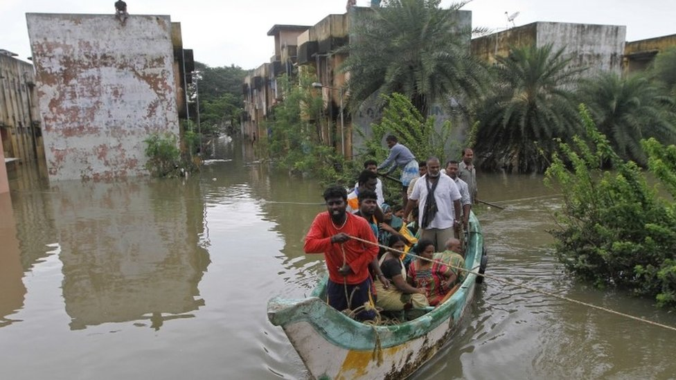 Volunteers rescue flood affected people on a country boat from a residential area in Chennai, India, Thursday, Dec. 3, 2015