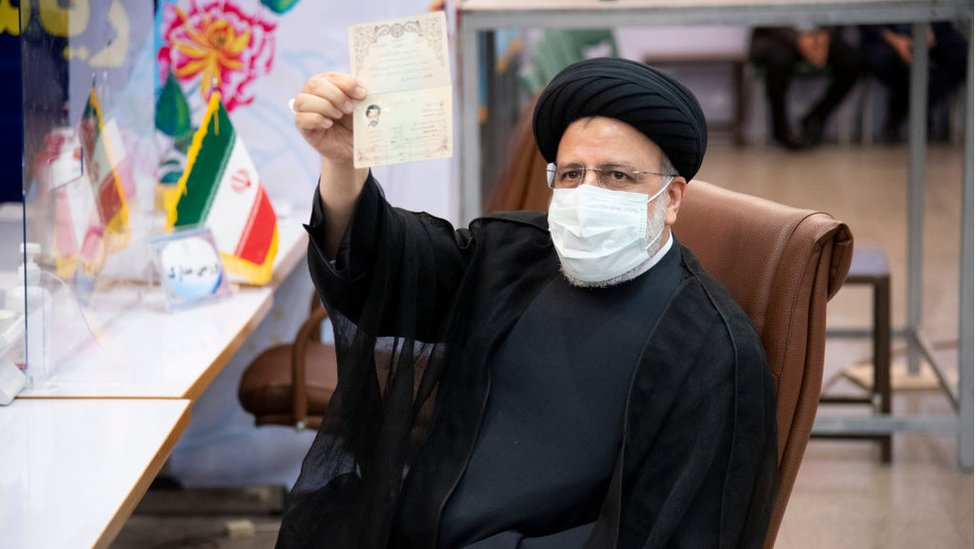 Ebrahim Raisi holds up his documents while registering as a candidate in the presidential election