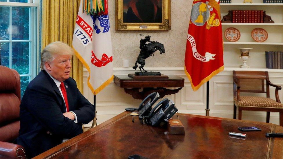 US President Donald Trump answers a reporter's question during an interview with Reuters in the Oval Office of the White House in Washington