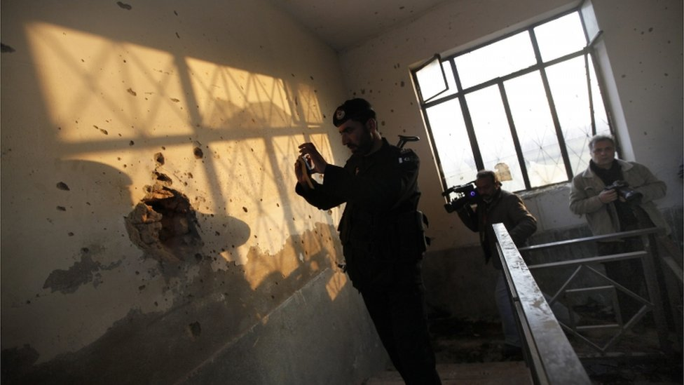 A Pakistani security official inspect the premises of Bacha Khan University