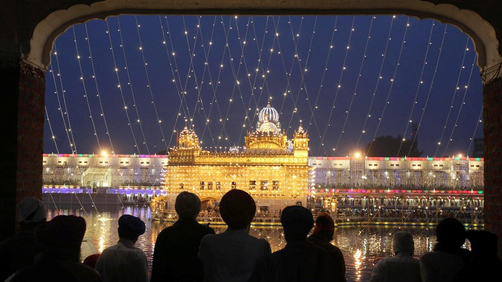 The Golden Temple lit up as Sikhs watch from a window