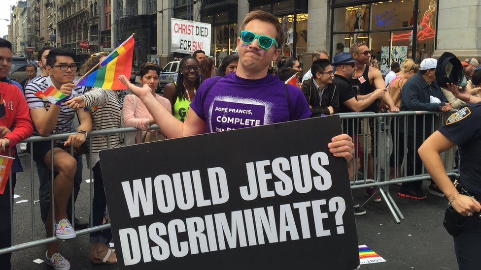 "A protestor with a signing saying ""Would Jesus discriminate?"""