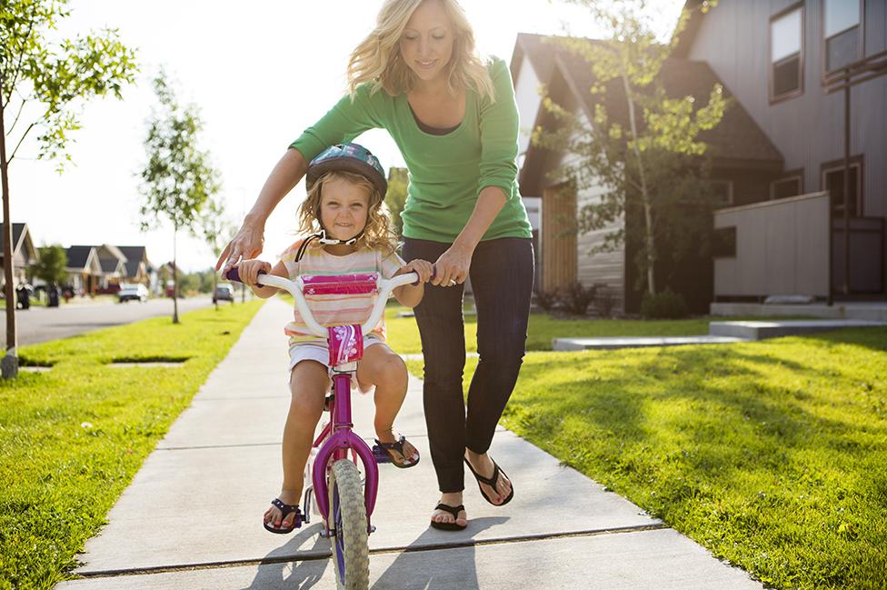 Una niña en bicicleta con su madre al lado
