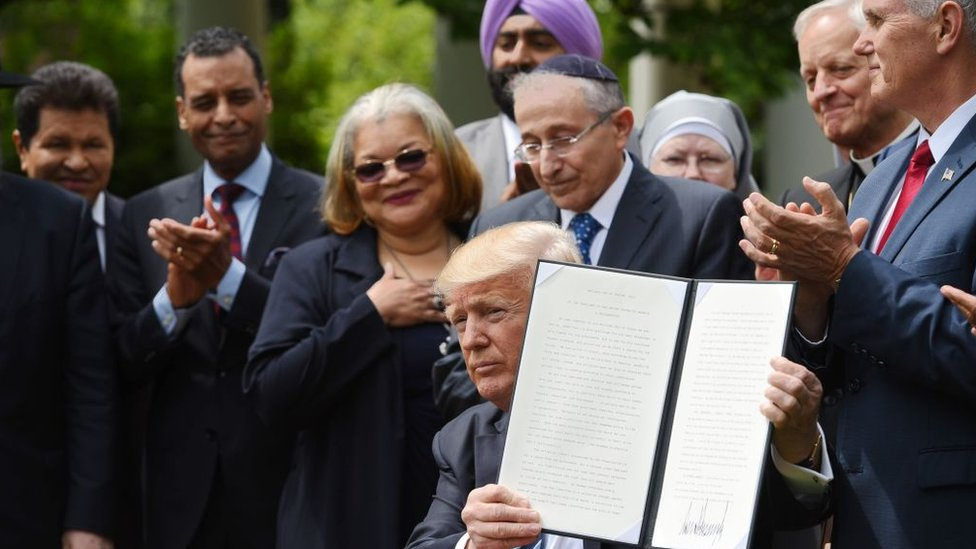 US President Donald Trump signs an executive order in the Rose Garden at the White House.