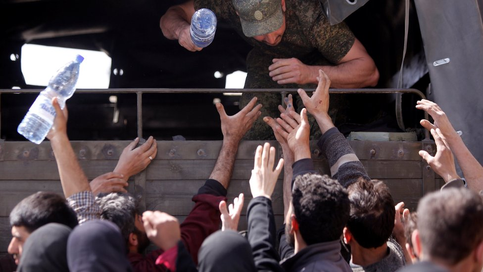 A Russian soldier distributes water to civilians who have fled the Eastern Ghouta, at a shelter in Adra, near Damascus, (20 March 2018)
