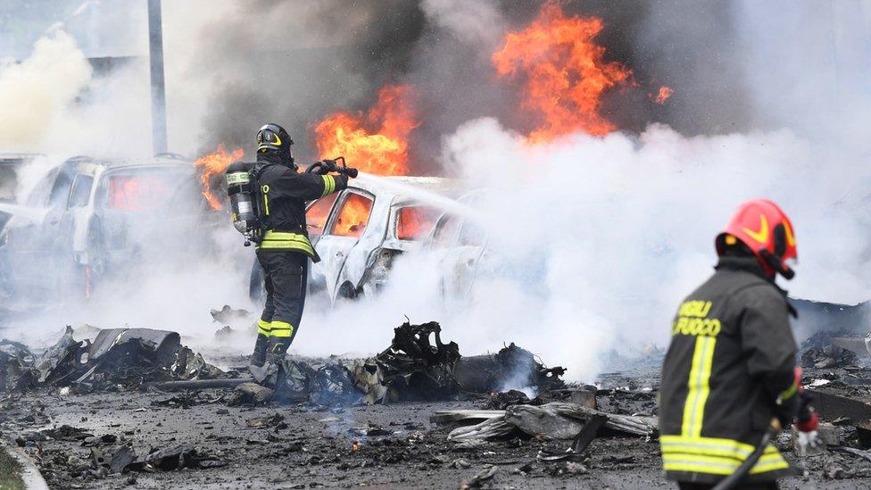 قوات الإطفاء تحاول إخماد النيران في سيارات مشتعلة