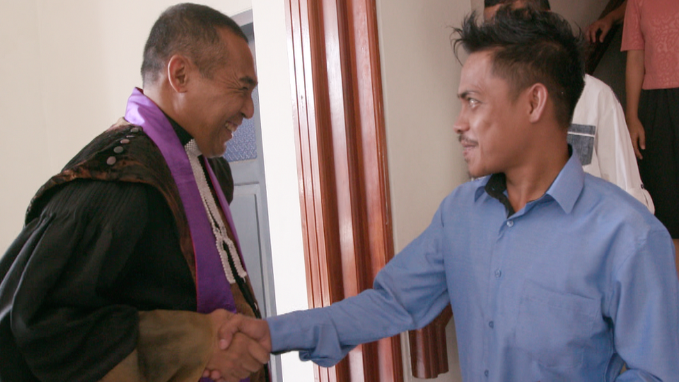 Rev Jacky Manuputty laughs as he shakes Ronald's hand in church