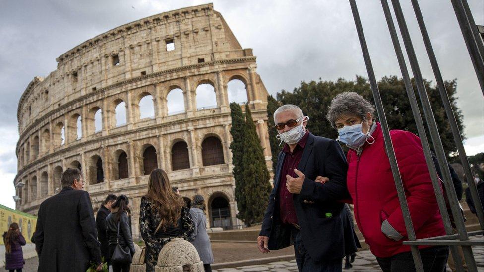 Personas con mascarillas faciales frente al coliseo de Roma.
