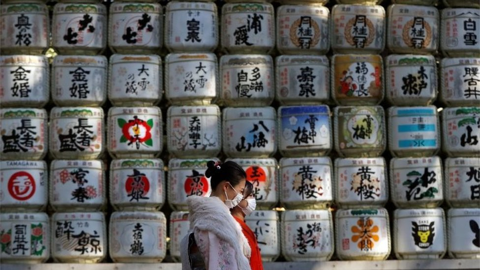Kimono-clad women wearing protective face masks walk in front of Japanese Sake barrel decorations for the year-end and New-Year at Meiji Shrine, amid the coronavirus disease (COVID-19) outbreak, in Tokyo, Japan, December 31, 2020.