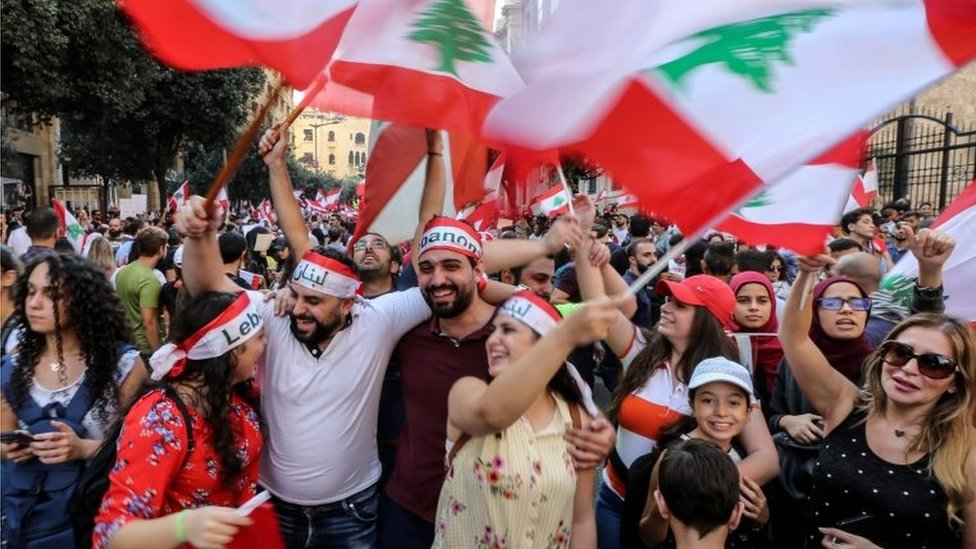 Protesters carry placards during a protest in front the government palace in downtown Beirut, Lebanon, on 20 October 2019.