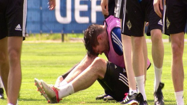 Kyle Lafferty looks in pain during Northern Ireland's training session in France