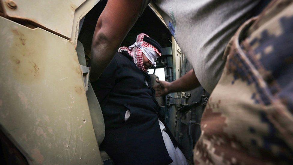 Un sospechoso de pertenecer a Estado islámico es introducido en un vehículo militar iraquí.