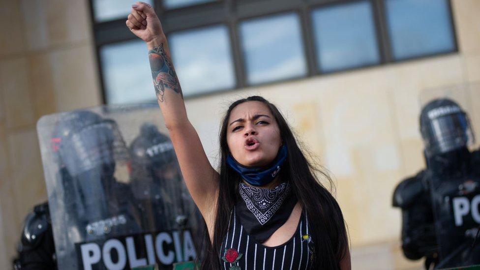 Mujer con el brazo levantado. Detrás la policía