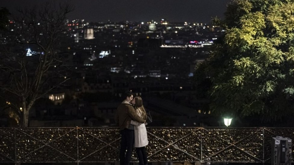 A couple wearing protective face masks embrace, in front of the Paris skyline seen from Montmartre at nightfall, just hours before a city-wide night time curfew goes into effect in Paris, France, 16 October 2020