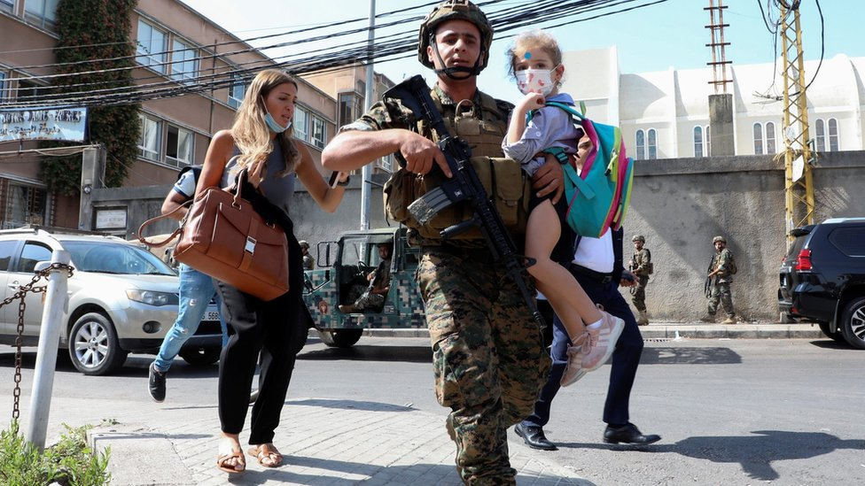 A Lebanese army soldier carries a schoolchild after gunfire erupts during protest against the judge investigating last year's blast at the city's port (14 October 2021)