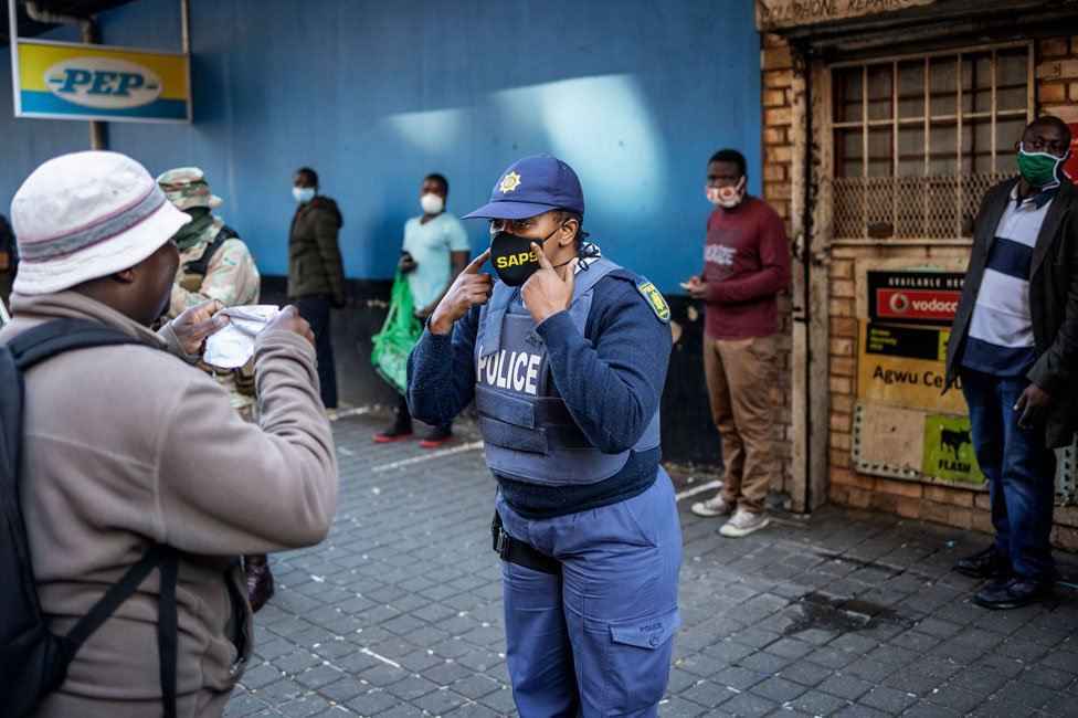 A policewoman shows someone how to put their mask on
