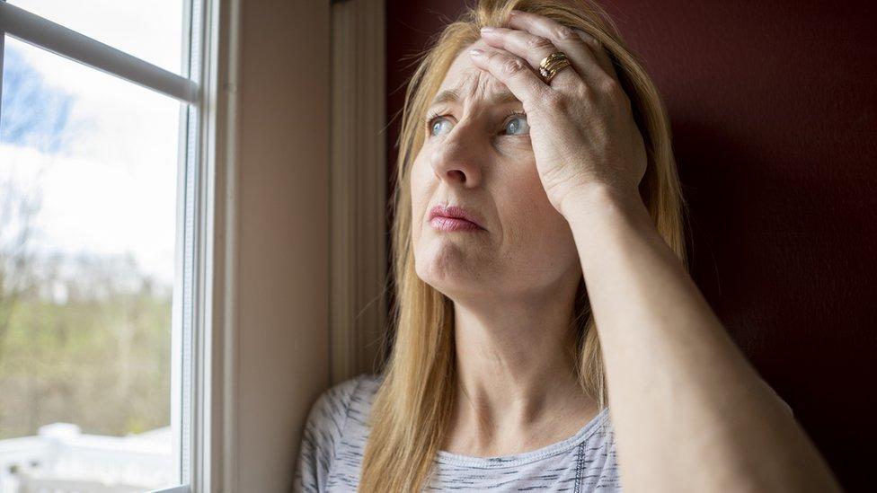 Mujer mirando a través de la ventana durante el confinamiento.