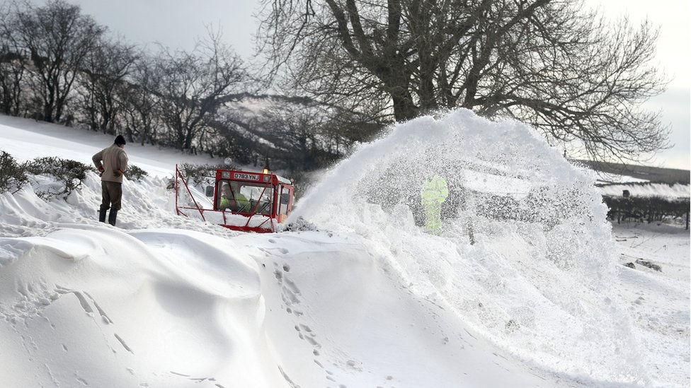 A homeowner watches over a snowblower as it clears the road which leads to the hamlet of Parkhead near Kirkoswald, Cumbria