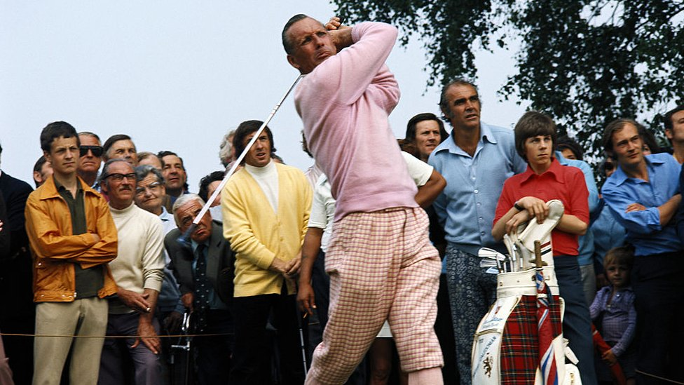 Max Faulkner - dressed in a pink sweater - swinging his golf club