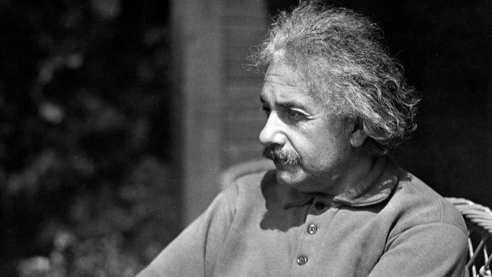 Einstein sentado vistiendo ropa informal y con la mirada perdida.