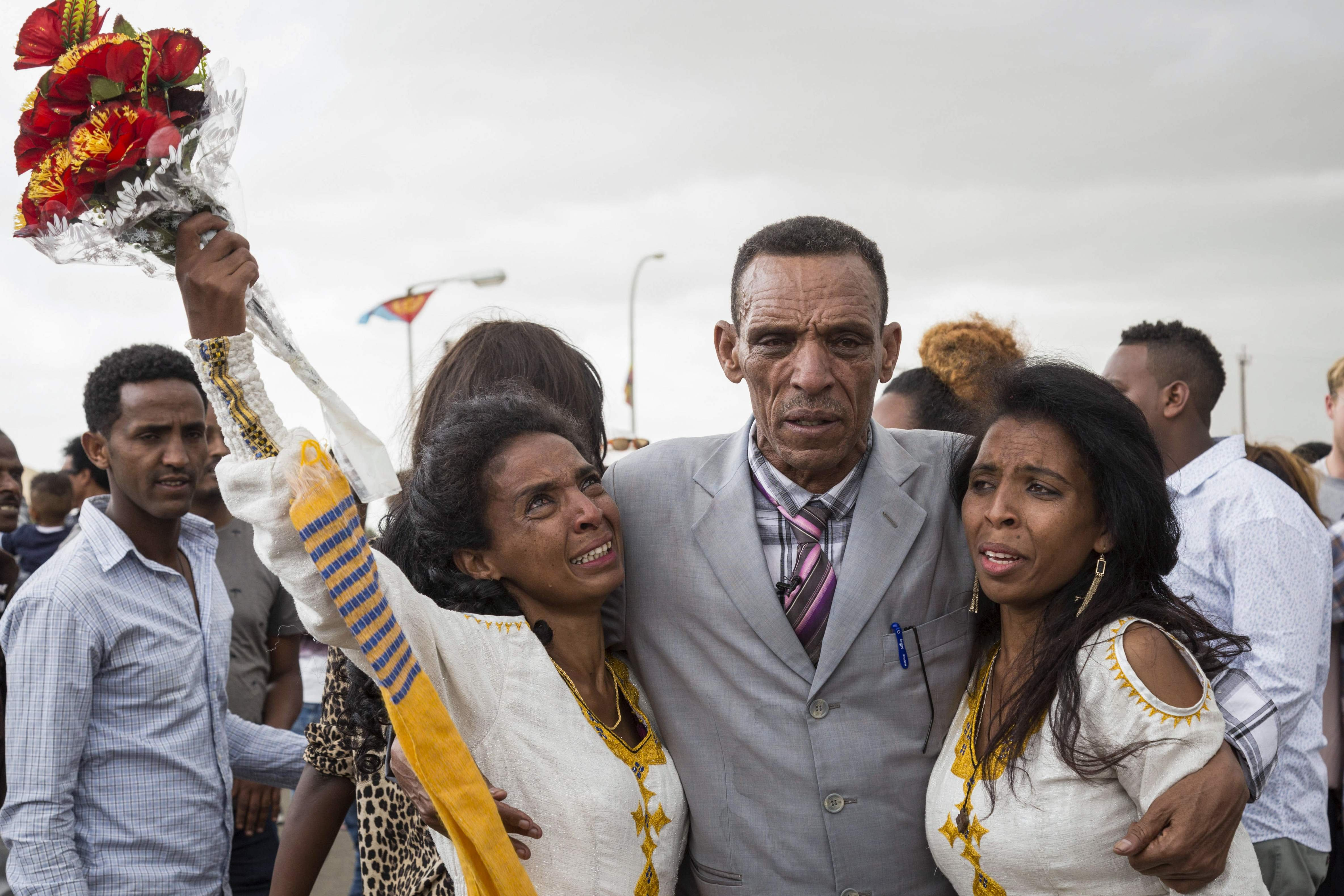 Azmera Addisalem and Danait Addisalem get emotional as they see again their father (who is an Ethiopian journalist) for the first time in 20 years, upon his arrival at the Asmara International airport, on July 18, 2018.
