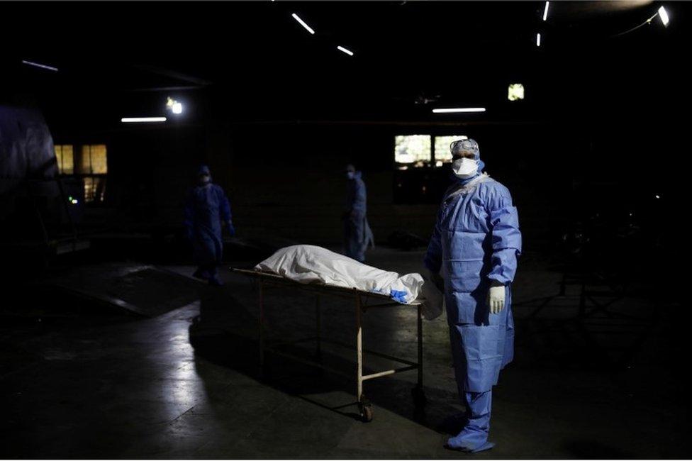 Un trabajador de la salud, vestido en traje de protección personal, espera frente al cuerpo de un hombre que murió de covid-19, antes de su cremación en Nueva Delhi, India, 21 de abril de 2021