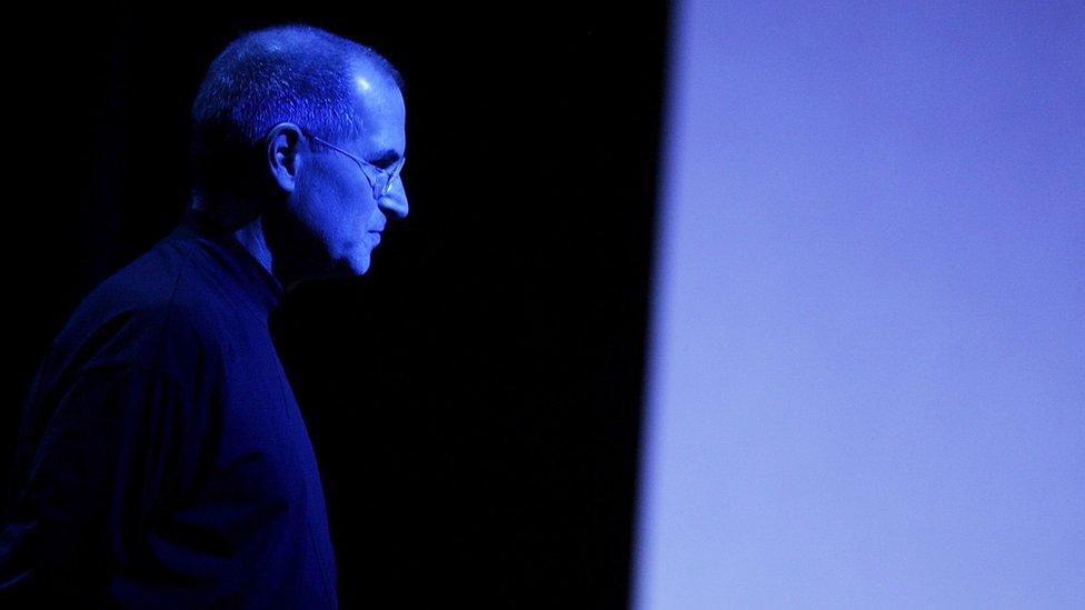 Steve Jobs lit up by blue lighting at a press event.