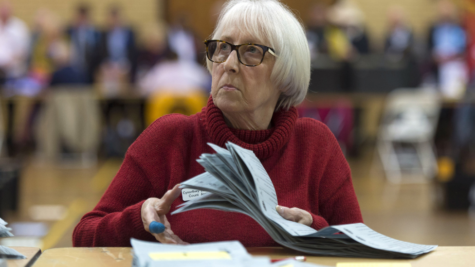A woman counts ballot papers at Llanishen Leisure Centre on May 4, 2017 in Cardiff, Wales.