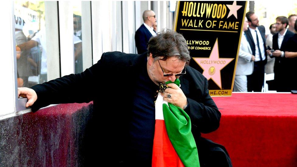Guillermo del Toro besando la bandera de México en el Paseo de la Fama.
