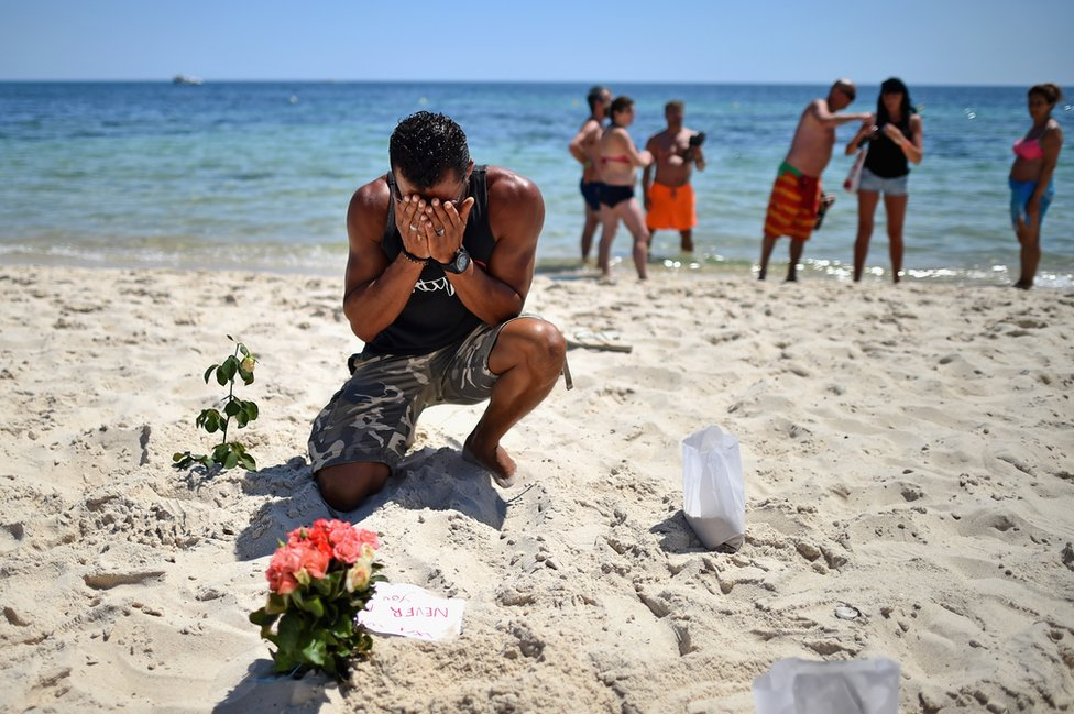 A man prays after laying flowers on Marhaba beach in Souuse, Tunisia