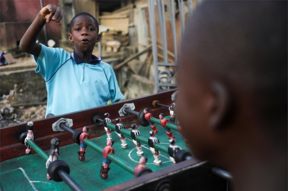 A child punches the air as he plays table football with others.