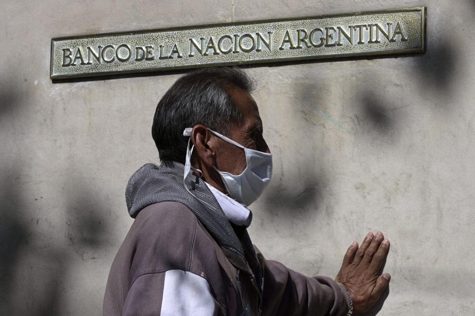Un hombre con tapabocas hace cola frente al Banco de la Nación Argentina.