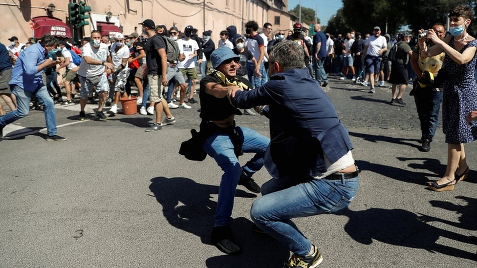 A plain-clothed police officer confronts a demonstrator as members of far-right political movements and hardcore football fans protest together against the economic crisis caused by the coronavirus outbreak and its handling by the Italian government, in Rome, Italy, on 6 June 2020