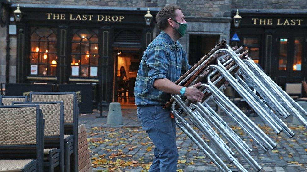 Pub worker stacking chairs in Edinburgh