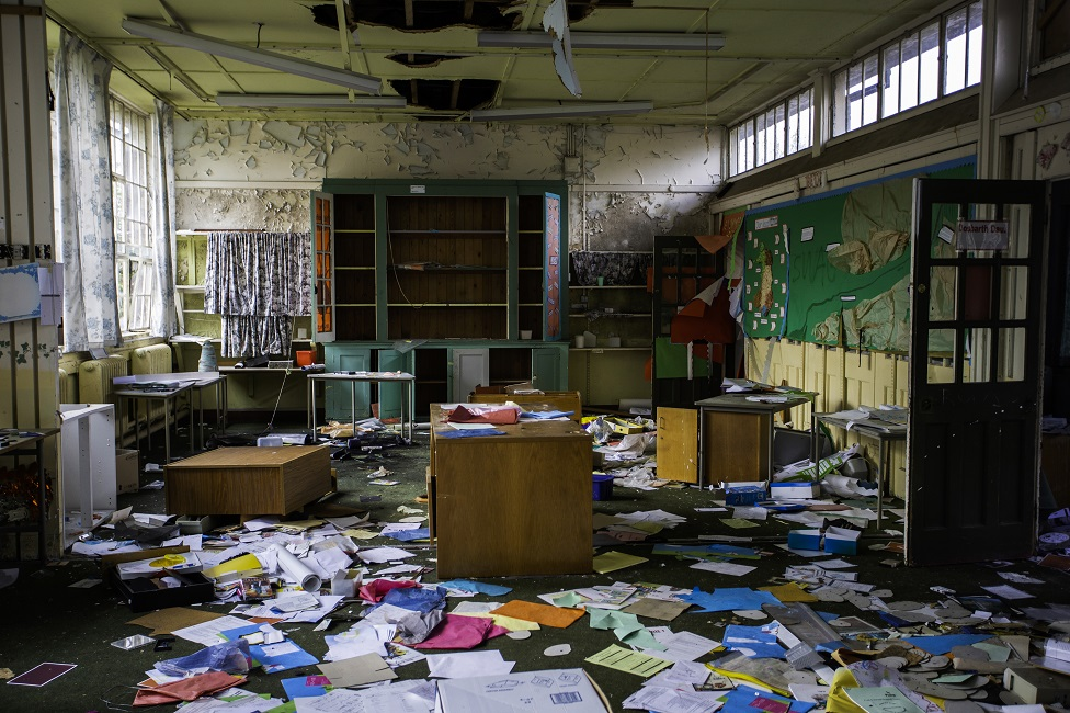 A derelict classroom with papers on the floor