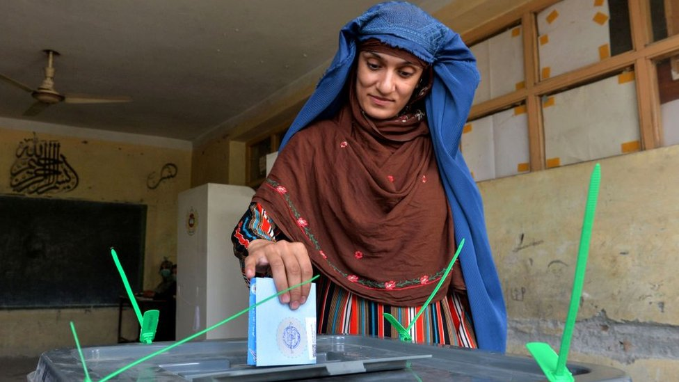 A woman casts her vote at a polling station in Jalalabad