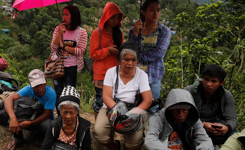 Relatives of those caught in the landslide wait as rescuers dig for bodies
