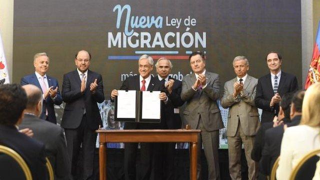 Piñera mostrando la nueva ley de migración.