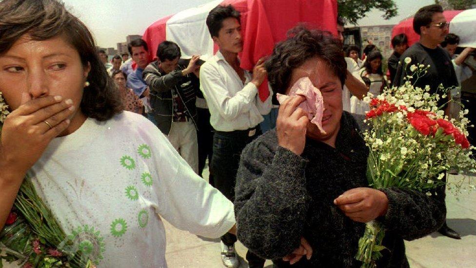 Familiares de policías asesinados por Sendero Luminoso llorando durante su funeral en la década del 90