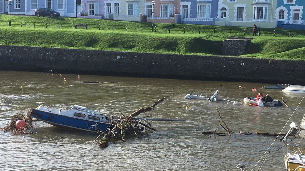 Boat in Aberaeron harbour covered in debris as people on another boat pull items from the water