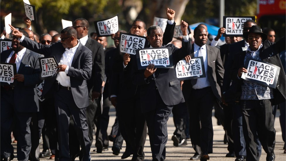 "This file photo taken on 19 January 2015 shows men holding signs reading ""Black Lives Matter"" march in the 30th annual Kingdom Day Parade in honour of Dr Martin Luther King Jr"