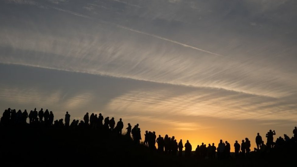 People standing on hill watching sunrise