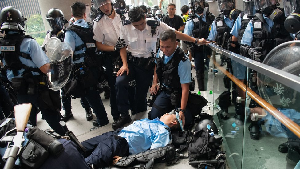 An injured Police officer lies on the floor during a protest against a proposed extradition law on June 12, 2019 in Hong Kong